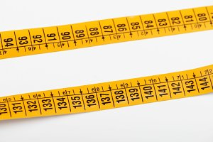 Yellow tape measure on white background. Isolated. Horizontal shoot.