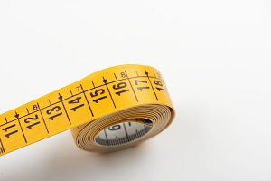 Tape measure yellow on white background. Copy space.
