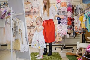 Mom and daughter admire a new dress in front of a mirror in a children's clothing store