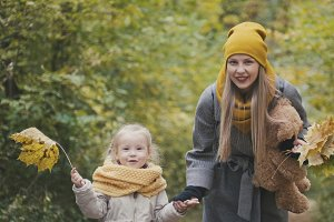 Blonde girl with her mommy in autumn park - play and clap hands