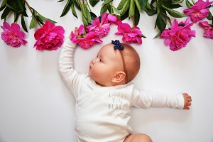Happy baby girl with a pink flower. Peony with child. Free place for text