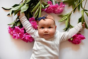 Peony with child. Free place for text. Happy baby girl with a pink flower