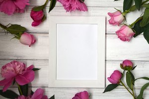 Stunning pink peonies on white rustic wooden background. Copy space. White frame for picture or photo