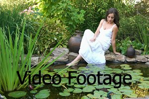 Girl sits on the shore of a pond