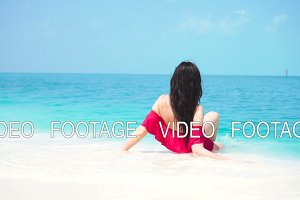 Young beautiful woman lying at shallow tropical water
