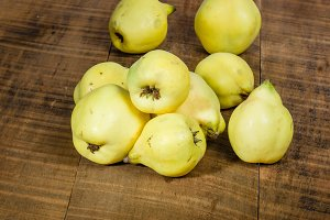 Ripe quince fruit on wooden table