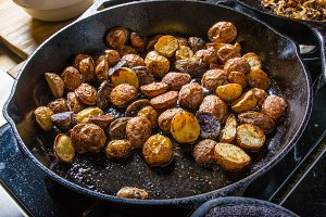 Cut potatoes frying in cast iron skillet