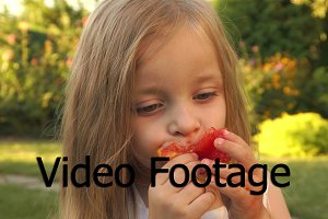 The girl is eating a tomato