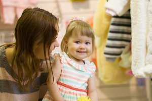 The little baby girl with mommy in clothes store