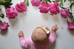 Little baby girl with pink peony on white background. Free place for text. Happy birthday. happy mother day. Happy father day
