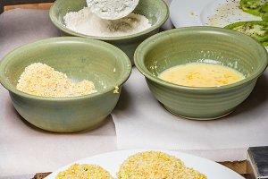 Applying cornmeal dredge to tomato slices