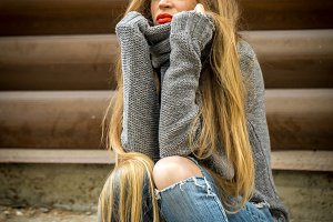 Beautiful girl in a sweater with long hair and red lips on the background of wooden logs