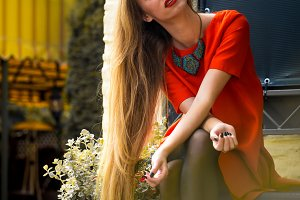 Fashionable girl in red dress and  lips with long hair sitting on the bench