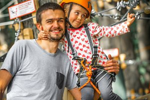sports happy child with father climbs over the ropes