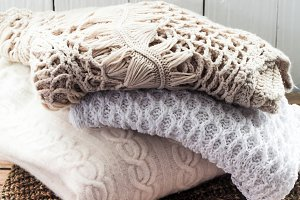 Knitted cosy sweater lying on wooden background