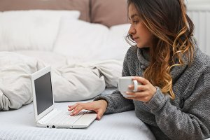 Girl in bed with a Cup and  computer