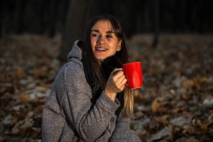 beautiful girl in autumn forest with a hot Cup of tea