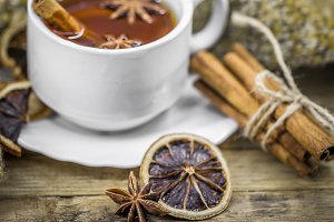 Cup of hot tea with cinnamon sticks and delicious dried lemon