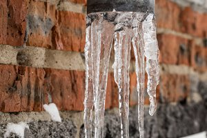 Natural icicles hanging on the pipe