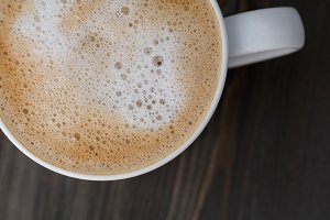 Top view of a white cup of cappuccino on a wooden black table. Close-up, macro shot. Copy space.