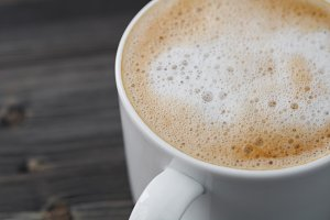 Close-up of a white cup of cappuccino on a wooden black table. Macro shot.