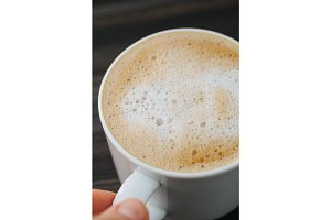 Hand holding a white cup of cappuccino on a wooden black table. Close-up, macro shot.