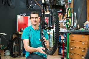 Male master is repairing the bicycle in a special workshop