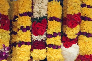 Garlands of colourful fresh flowers hanging up outside a stall. Traditional garlands at Indian market to worship the sacred