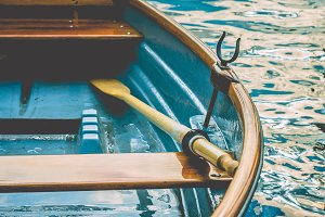 Close up of an wooden pleasure rowboat at the pier of a lake