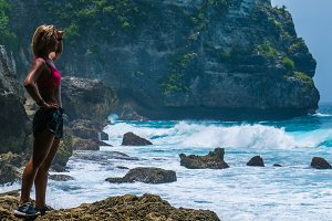 Girl standing on Tembeling Beach with view of coastline at Nusa Penida island, Bali Indonesia
