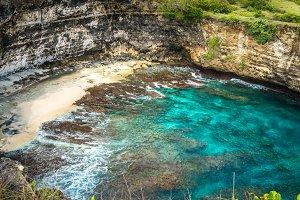 Small Sandy Beach in front iof Stone arch over the sea. Broken beach. Rock coastline. Nusa Penida, Indonesia