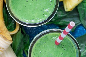 Detox green smoothie with spinach, pineapple, banana and yogurt, vertical, top view, closeup
