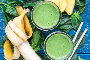 Detox green smoothie with spinach, pineapple, banana and yogurt, vertical, top view