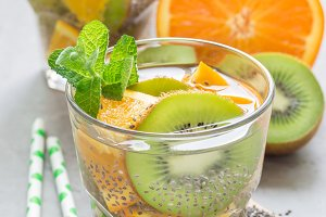 Healthy detox chia seed drink with kiwi, orange and mint in a glass, vertical