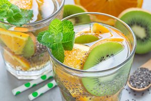 Healthy detox chia seed drink with kiwi, orange and mint in glass, horizontal, closeup