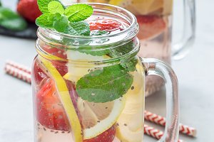 Healthy detox chia seed drink with strawberry, lemon and mint in a glass jar, vertical