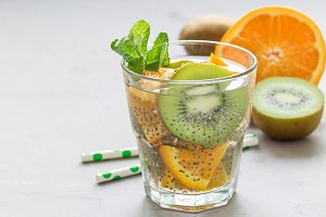 Healthy detox chia seed drink with kiwi, orange and mint in a glass, horizontal, copy space