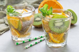 Healthy detox chia seed drink with kiwi, orange and mint in glass, horizontal