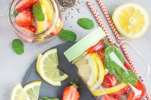 Healthy detox chia seed drink with strawberry, lemon and mint in a glass jar, vertical, top view
