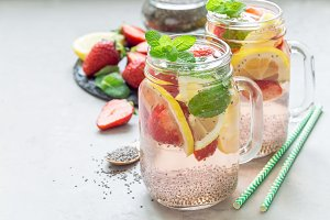 Healthy detox chia seed drink with strawberry, lemon and mint in a glass jar, horizontal, copy space