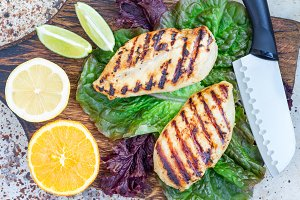Grilled chicken breast on salad leaves and wooden cutting board, horizontal, top view