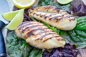 Grilled chicken breast on salad leaves, horizontal
