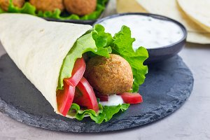 Chickpea falafel balls with vegetables and white sauce, roll sandwich preparation, horizontal, copy space