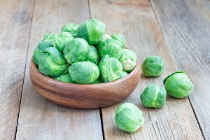 Brussels sprouts in a bowl on wooden background, horizontal