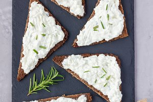 Pumpernickel bread with feta, cream cheese, rosemary, lemon and garlic dip, on slate board, top view, vertical