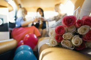 Party in limousine - happy girls celebrating, women drinks champagne - in front of bouquet of roses