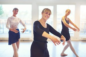 Smiling adult women standing and performing ballet in class