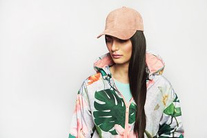 Pretty girl in fashionable jacket and pink cap