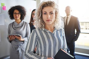 Business woman standing in front of colleagues