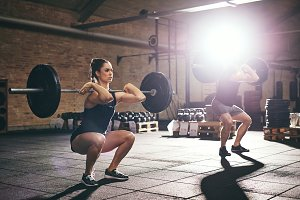 Fit people training lift barbells in gym